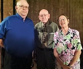 Bob Baker visits with Charlie Logan and Program Vice President Reba Phillips Welch